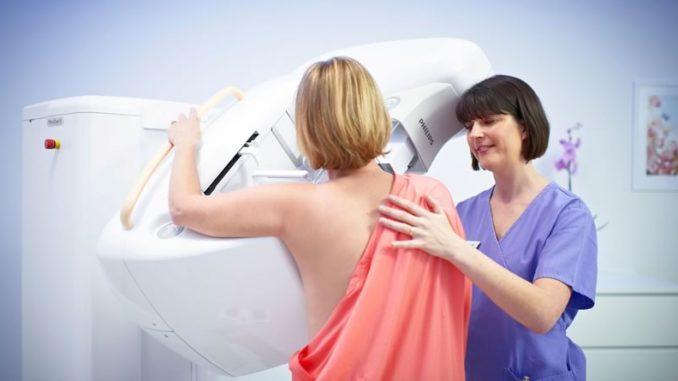 Помощь доктора при проведении маммографии груди у женщины.